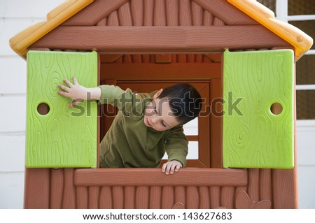 Small child playing with window in a toy playhouse in an yard or an outdoor playground. - stock photo