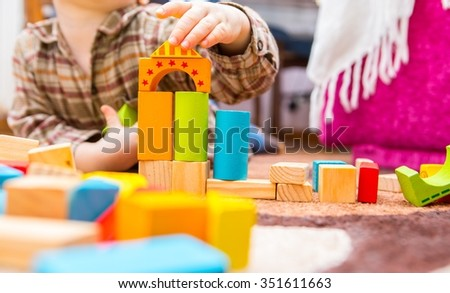 Small child playing with wooden blocks. Caucasian boy building with blocks - stock photo