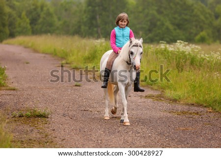 Small child riding on a white horse on the road - stock photo