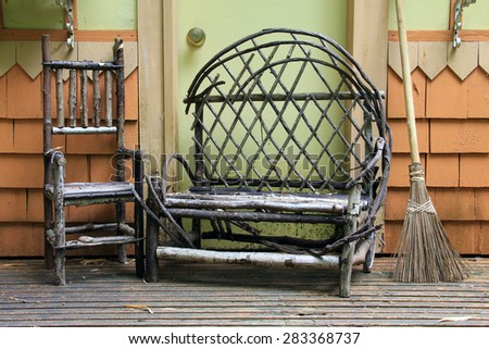 Small child size chair and loveseat made from tree branches on an wood porch.  - stock photo