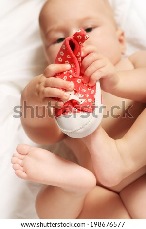 Small child tries to put on his shoes. Baby boy with shoes in hand - stock photo