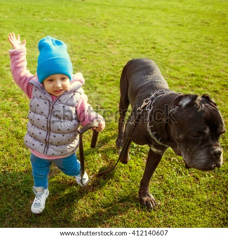 small child walking with a dog on a leash on the grass in the park - stock photo