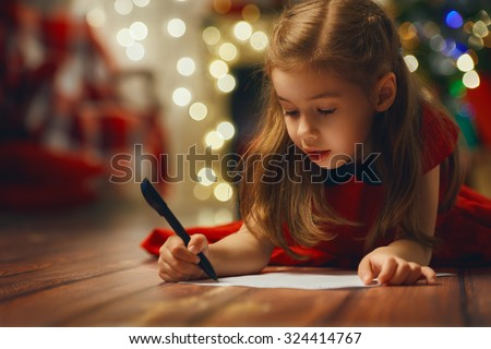 small child writes the letter to Santa - stock photo