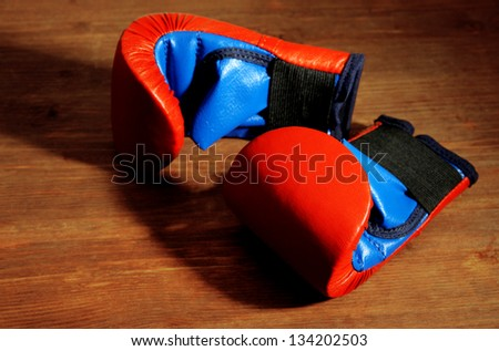 Small children boxing gloves on wooden background - stock photo