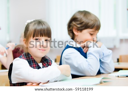 Small children sit in desks - stock photo