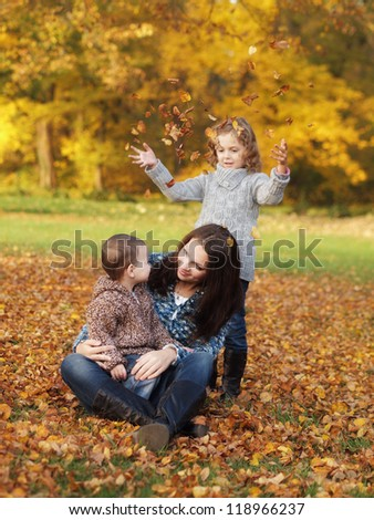 small children with mother playing in the park in autumn - stock photo