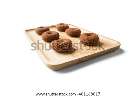 Small chocolate donut on wooden plate on white background - stock photo
