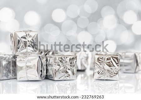 Small Christmas gifts in shiny silver paper, bokeh lights background - stock photo