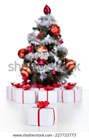 Small Christmas present with fir tree and other gifts in background - isolated - stock photo