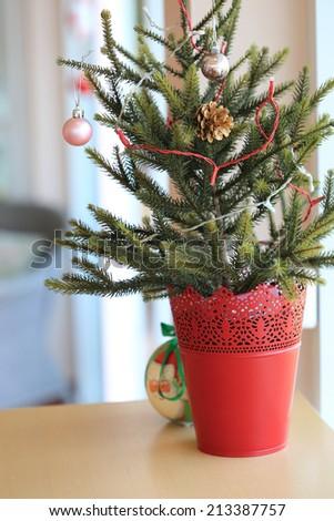 small christmas tree decoration on table - stock photo