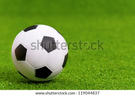 Small classic soccer ball on green artificial grass - stock photo