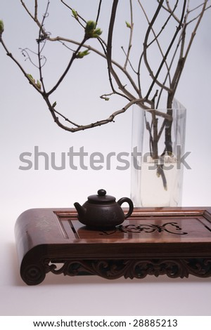 small clay teapot with glass vase - stock photo