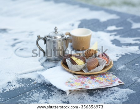 Small coffee pot and assorted sweets laid on a frozen table, winter coffee time. Selective focus shot - stock photo