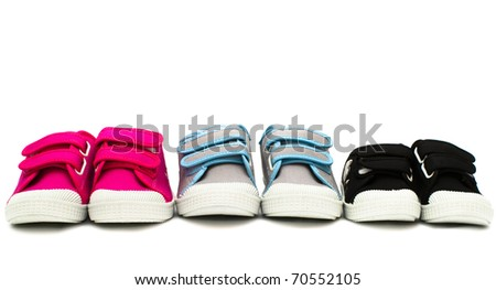 Small color children shoes isolated on white background in row - stock photo