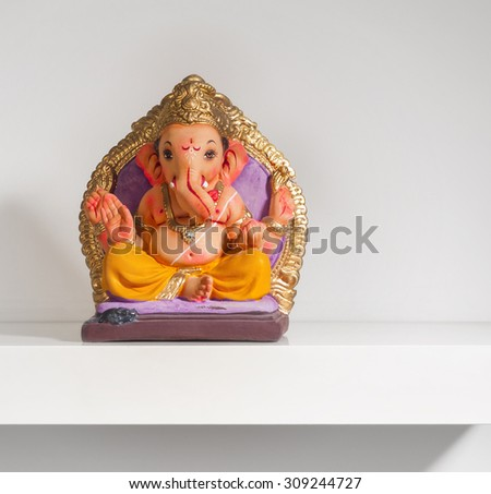 Small colorful Ganesha idol placed on a white shelf. - stock photo
