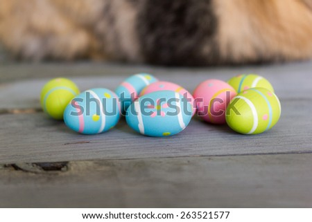 Small colorful painted easter eggs randomly placed on a wooden table with blurred bunny in the background. - stock photo