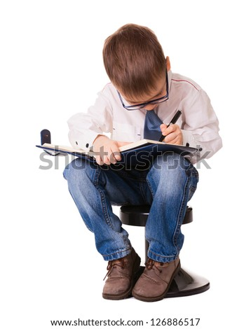 Small concentrated kid write down in organizer notebook with pen. Isolated on white background. - stock photo