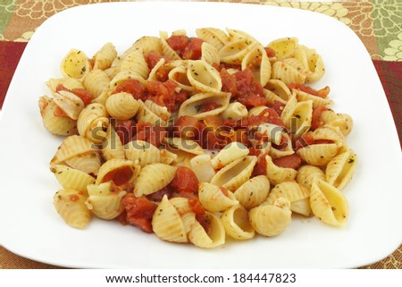 Small conchigliette pasta shells prepared with diced tomatoes, many peeled garlic cloves, parsley, basil and oregano served on a white plate with a colorful background. - stock photo