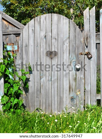 Small country style gate. Locked wicket to the house. Village door wooden planks with decorative hole shape sweet heart - stock photo