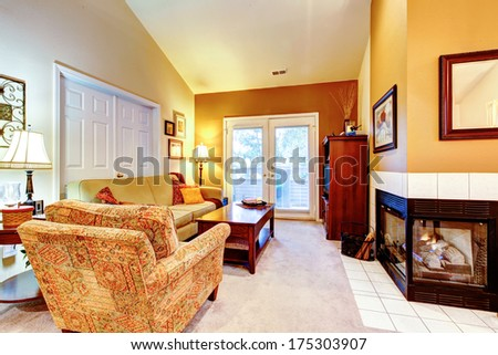 Small cozy living room with fireplace, wood coffee table and cabinet, mustard sofa and chairs. - stock photo
