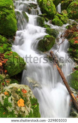 Small creek flowing amongst rocks and green moss in autumn - stock photo