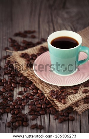 Small cup of espresso with coffee beans on dark wooden background, selective focus - stock photo