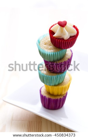 small cupcake in colorful cup place one on top of the other to create a column with a top cupcake with valentine inspire decoration - stock photo