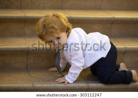 Small curious stylish baby boy with blonde curly hair in formal white shirt grey necktie and trausers crawling barefoot on brown stone stairs looking away, horizontal picture - stock photo