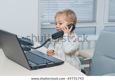 Small cute business boy with phone and computer in office - stock photo
