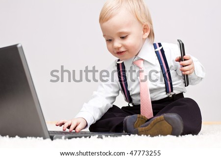 Small cute businessman with cellphone working on laptop - stock photo