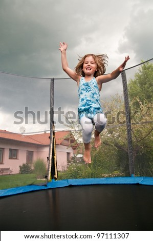 Small cute child jumping on trampoline - garden and family house in background - stock photo