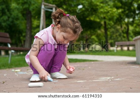 Small cute girl drawing with chalk on sidewalk, trees in background - stock photo