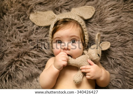 Small cute girl playing with her favorite rabbit toy - stock photo