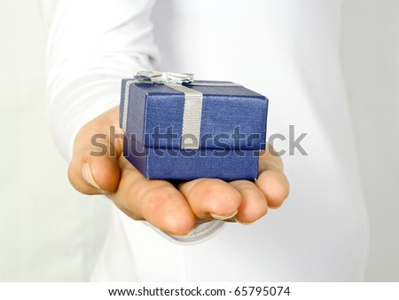 Small dark blue gift in a female hand - stock photo