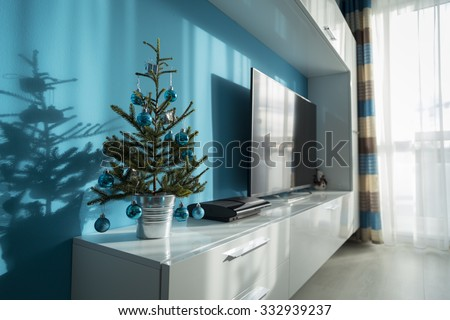 small decorated Christmas tree in a bucket on the furniture in the living room in a pleasant interior, tuned in the colors turquoise - stock photo