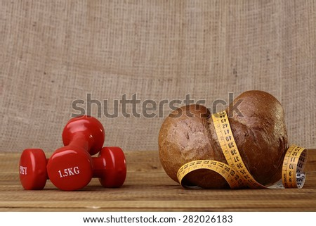 Small delicious dietary bun and yellow tape measure with two lottle red dumbbells as a symbol of diet lie on the table on brown background copy space, horizontal photo - stock photo