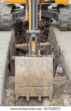 Small digger in city digging trench, utility repair - stock photo