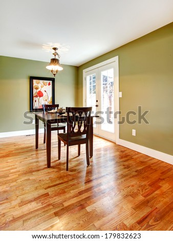 Small dining room with a hardwood floor and olive walls. Furnished with a black dining table set. - stock photo