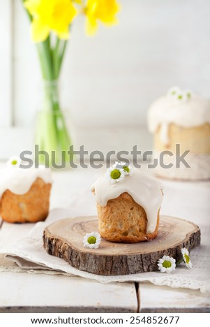 Small Easter cake, kulich, cross bun on a white spring background. Traditional Russian Easter cake. - stock photo