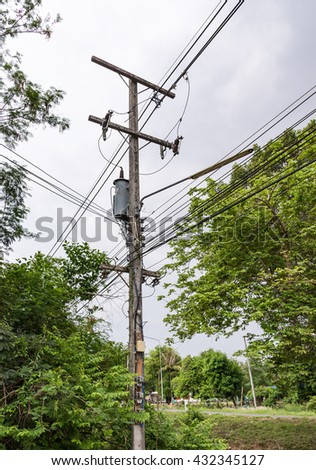 Small electric transformer on the electricity post in the rural of Thailand. - stock photo