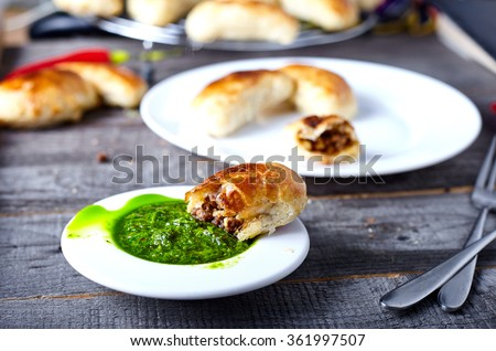 Small empanadas with meat on a white plate. - stock photo