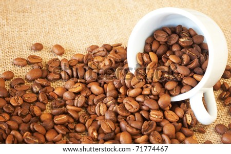 Small espresso cup filled with roasted coffee beans - stock photo