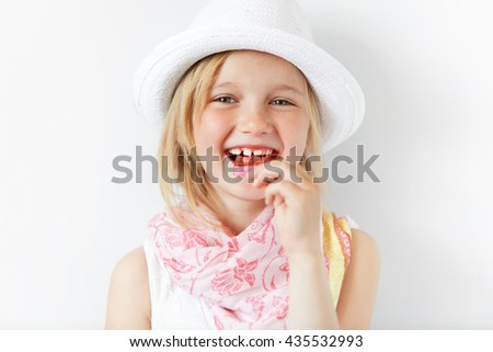 Small European girl laughing at camera and eating lollipop in white morning light. Holiday mood and cheerful atmosphere mixed with shinny white look of kid and her happy-go-lucky style. - stock photo