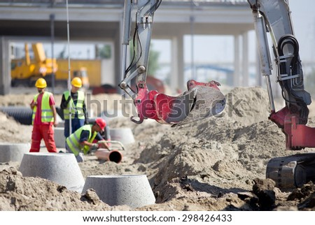 Small excavator and workers at construction site - stock photo