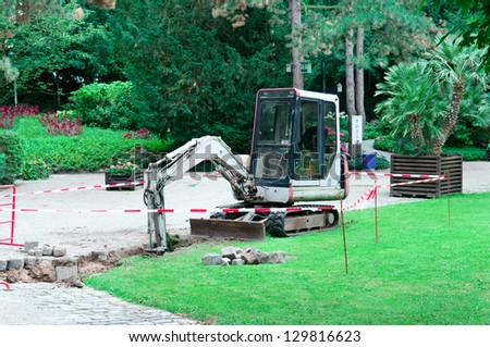 small excavator working in the park - stock photo