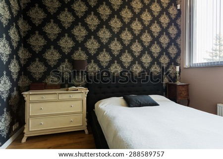 Small exclusive oriental decorated bedroom with black bed - stock photo