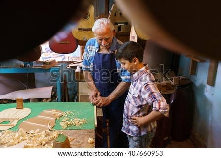 Small family business and traditions: old grandpa with grandson in lute maker shop. The senior artisan teaches to the boy how to chisel wood to make a music instrument - stock photo