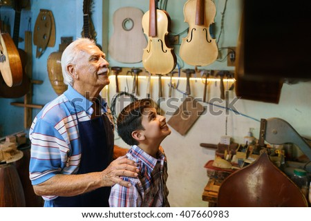 Small family business and traditions: old grandpa with grandson in lute maker shop. The senior artisan hugs the boy and shows him his handmade guitar and music instruments. - stock photo