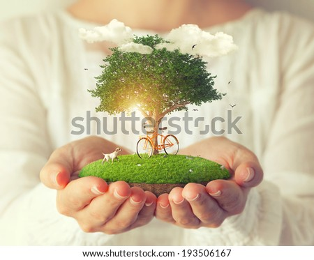 Small fantastic island with a bicycle under the tree in women's hands. - stock photo
