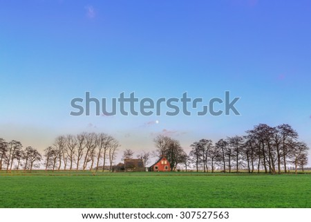Small farm in a winter evening landscape with meadows - stock photo